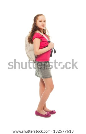 Portrait of happy, smiling, confident 9 years old girl with curly hair, wearing backpack isolated on white - full height portrait, side view - stock photo