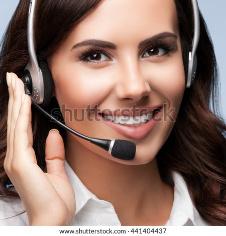 Portrait of happy smiling customer support female phone operator in headset, against grey background. Consulting and assistance service call center. - stock photo