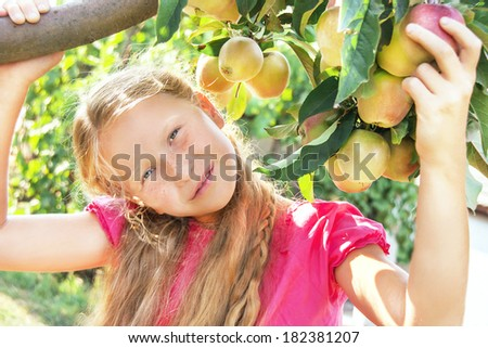 Portrait of happy smiling cute child (girl) near apple tree on beautiful day. Kid has healthy food outside in summer dress. Outdoor. Close up. - stock photo