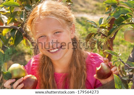 Portrait of happy smiling cute child (girl) with green and red fresh apples near apple tree on beautiful day. Kid has healthy food outside in summer dress and laughing. Outdoor. Close up. - stock photo