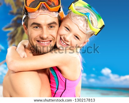 Portrait of  happy smiling father hugs daughter 9 years old at tropical beach - stock photo