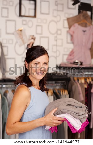 Portrait of happy smiling female customer holding stack of clothes in boutique - stock photo