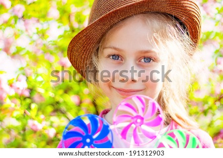 Portrait of happy smiling five years old caucasian blond child girl in a hat on blooming garden background. Spring - careless childhood, playing windmill. - stock photo