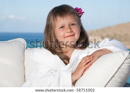 Portrait of happy smiling little girl with flowered hair in white bathrobe relaxing on terrace divan and looking at camera on the sea background - stock photo