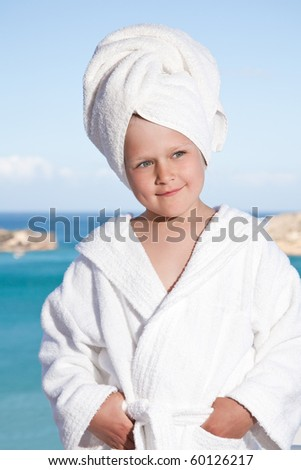 Portrait of happy smiling little girl with towel on the head in white bathrobe relaxing on terrace on the sea background - stock photo