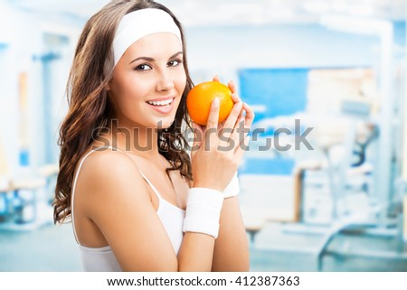 Portrait of happy smiling lovely woman with orange, at fitness center or gym - stock photo
