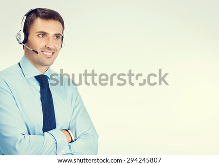 Portrait of happy smiling male customer support phone operator in headset, in blue confident business wear, with blank copyspace area for slogan or text message - stock photo