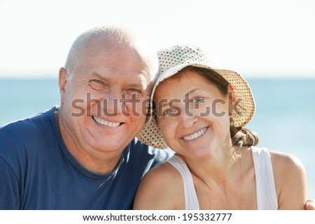 Portrait of Happy smiling mature couple against sea and sky - stock photo
