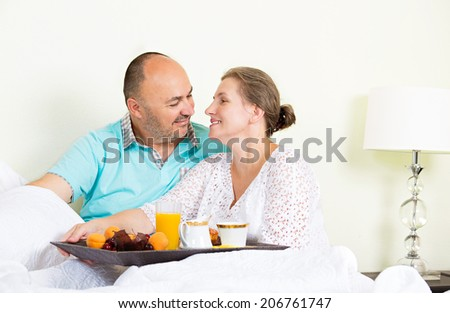 Portrait of happy, smiling middle aged couple enjoying one another while having breakfast in bed, vacation times, isolated hotel, house bedroom. Positive human emotions, face expressions, feelings - stock photo