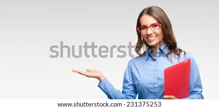 Portrait of happy smiling showing businesswoman in glasses with red folder, against grey background, with copyspace  - stock photo