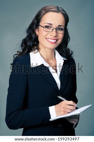 Portrait of happy smiling thinking business woman with notepad or organizer, over gray background - stock photo