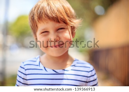 Portrait of happy smiling toddler child kid outdoors. Closeup, focus on eyes. - stock photo