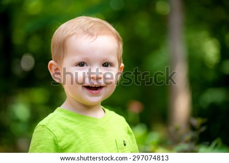 Portrait of happy smiling toddler playing outdoors - stock photo