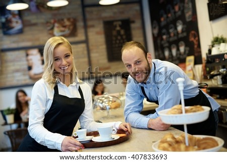 Portrait of happy smiling waiter and waitress in cafeteria elbowing on counter. - stock photo