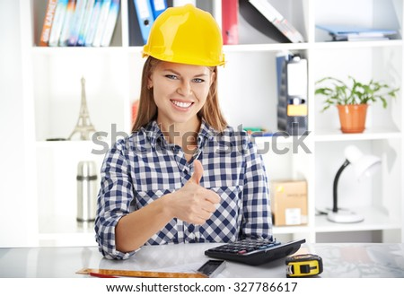 Portrait of happy smiling woman engineer wearing protective helmet showing thumb up at workplace.  - stock photo