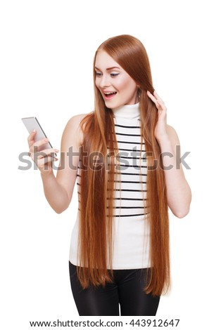 Portrait of happy smiling woman looking at mobile excited. Young redhead long-haired girl get message on cell phone. Female portrait isolated at white, modern communication technology concept. - stock photo