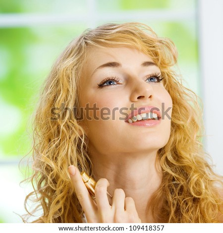 Portrait of happy smiling young beautiful blond woman with perfum bottle at home - stock photo