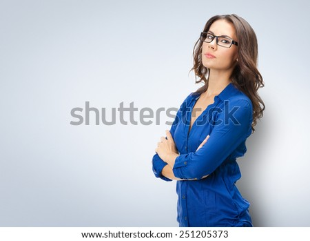 Portrait of happy smiling young beautiful businesswoman in glasses, with copyspace area - stock photo
