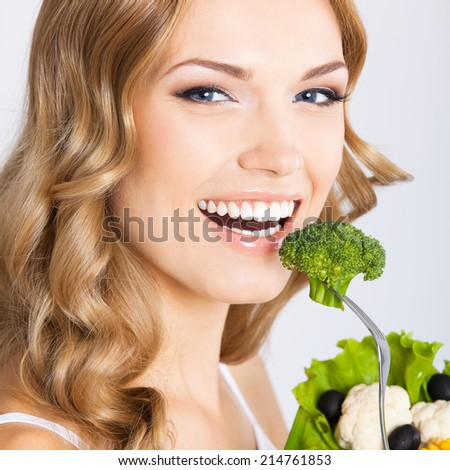 Portrait of happy smiling young beautiful woman eating broccoli, over gray background - stock photo