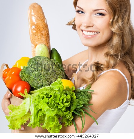 Portrait of happy smiling young beautiful woman with healthy vegetarian raw food, over gray background - stock photo