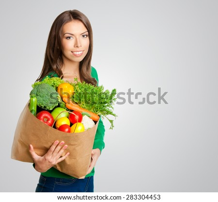 Portrait of happy smiling young beautiful woman with shopping bag of healthy vegetarian raw food, with copyspace blank empty area for text or slogan, against grey background - stock photo