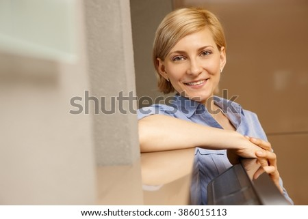 Portrait of happy smiling young blonde woman looking at camera. - stock photo