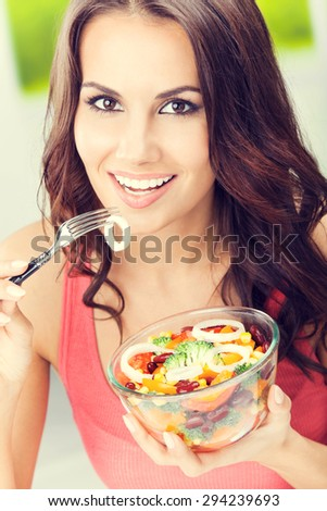 Portrait of happy smiling young brunette woman with vegetarian vegetable salad, outdoors - stock photo