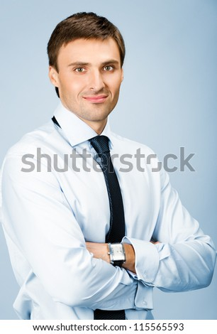 Portrait of happy smiling young business man, over blue background - stock photo
