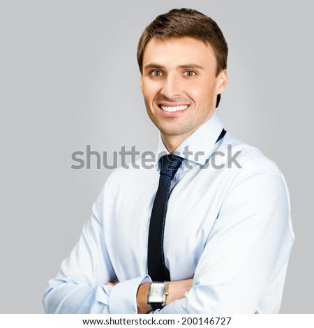 Portrait of happy smiling young business man, over gray background - stock photo