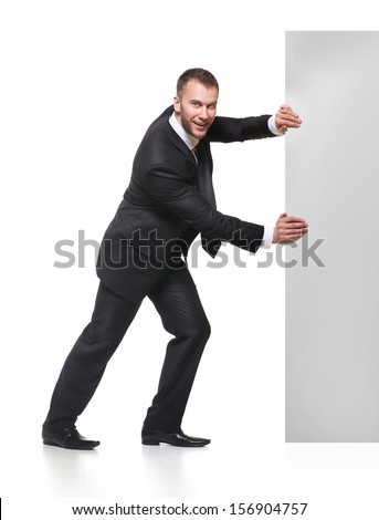 Portrait of happy smiling young business man pushing blank signboard isolated on white background - stock photo