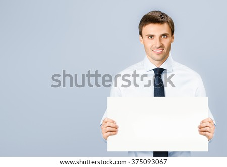 Portrait of happy smiling young business man showing blank signboard, with copyspace, over grey background - stock photo