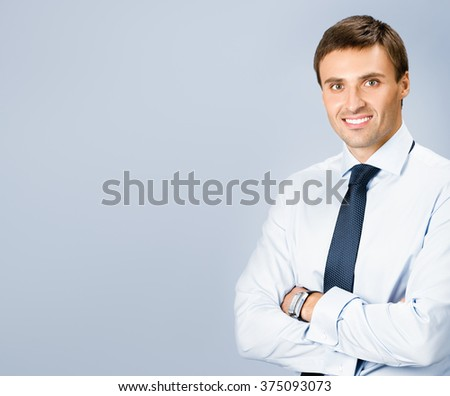 Portrait of happy smiling young business man, with copyspace, over grey background - stock photo