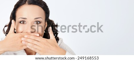 Portrait of happy smiling young business woman covering with hand her mouth, against grey background, with copyspace - stock photo
