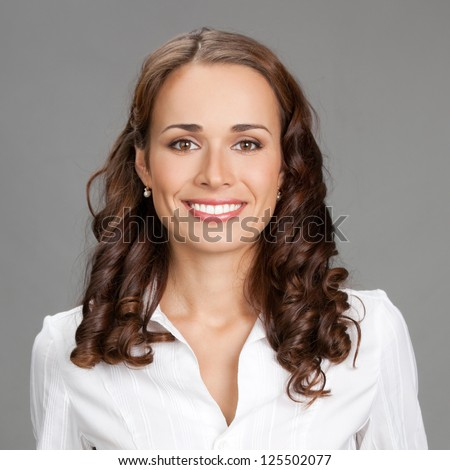 Portrait of happy smiling young business woman, over gray background - stock photo