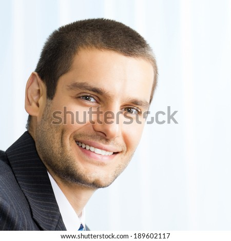 Portrait of happy smiling young businessman at office - stock photo
