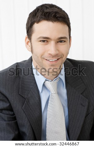 Portrait of happy smiling young businessman at office. - stock photo