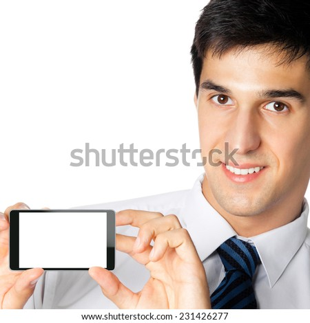 Portrait of happy smiling young businessman showing blank cellphone, isolated against white background - stock photo