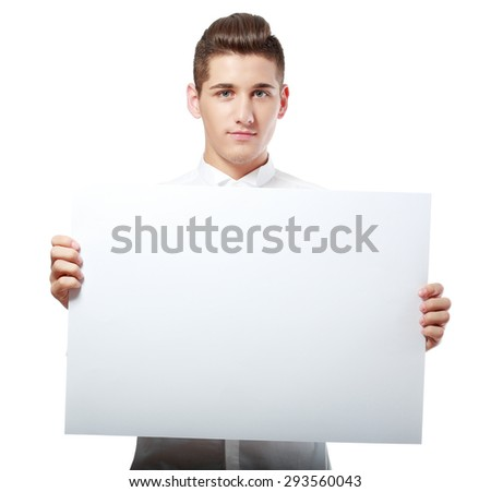 Portrait of happy smiling young businessman showing blank signboard, with copyspace area for text or slogan, against grey background - stock photo