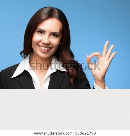 Portrait of happy smiling young businesswoman in black suit, showing blank signboard, over blue background, showing okay gesture - stock photo