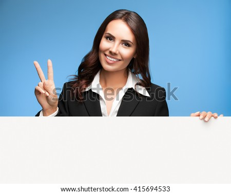 Portrait of happy smiling young businesswoman in black suit, showing blank signboard with blank copyspace area for slogan or text, over blue background, showing two fingers or victiory gesture - stock photo