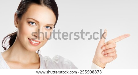 Portrait of happy smiling young businesswoman showing something or copyspase for product or sign text, over grey - stock photo