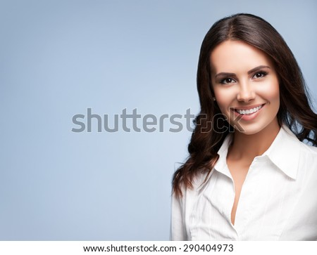 Portrait of happy smiling young cheerful brunette businesswoman, with blank copyspace area for slogan or text message, over grey background - stock photo