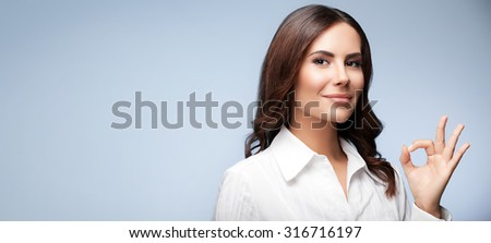 Portrait of happy smiling young cheerful businesswoman, showing okay hand sign gesture, with blank copyspace area for slogan or text message, over grey background - stock photo