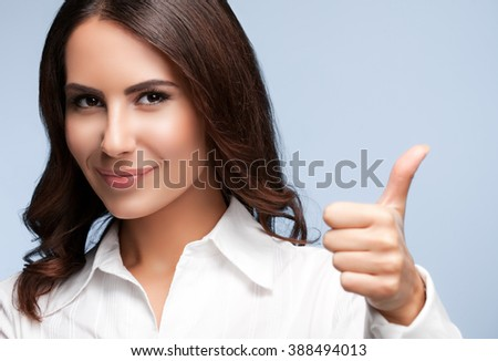 Portrait of happy smiling young cheerful businesswoman, showing thumb up hand sign gesture , over grey background - stock photo