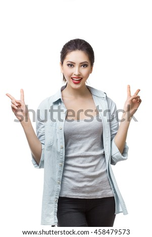Portrait of happy smiling young cheerful woman, showing two fingers or victory gesture, on white isolated background. Young woman Asian Caucasian students - stock photo