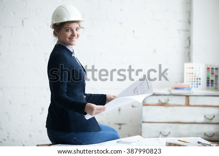 Portrait of happy smiling young engineer woman in white hard hat sitting on office desk in architectural agency.Model holding project plan, looking at camera with friendly expression. Copy space - stock photo