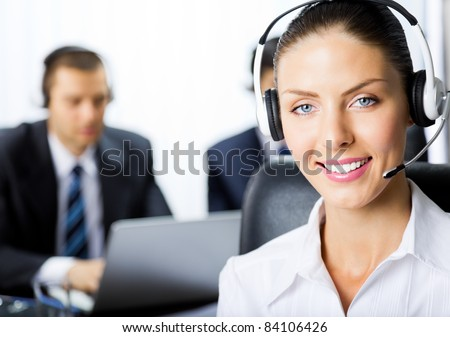 Portrait of happy smiling young female customer support phone operator in headset at office - stock photo