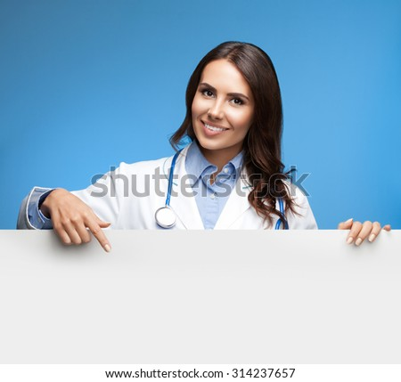 Portrait of happy smiling young female doctor showing blank signboard, over blue background - stock photo