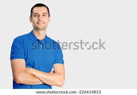Portrait of happy smiling young man, against grey background - stock photo