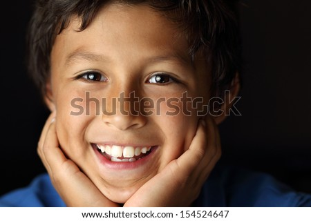 Portrait of happy smiling young school boy with face resting in hands with chiaroscuro lighting - shallow depth of field - stock photo